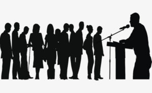 Siluetas de una persona hablando ante un micro y su audiencia escuchando