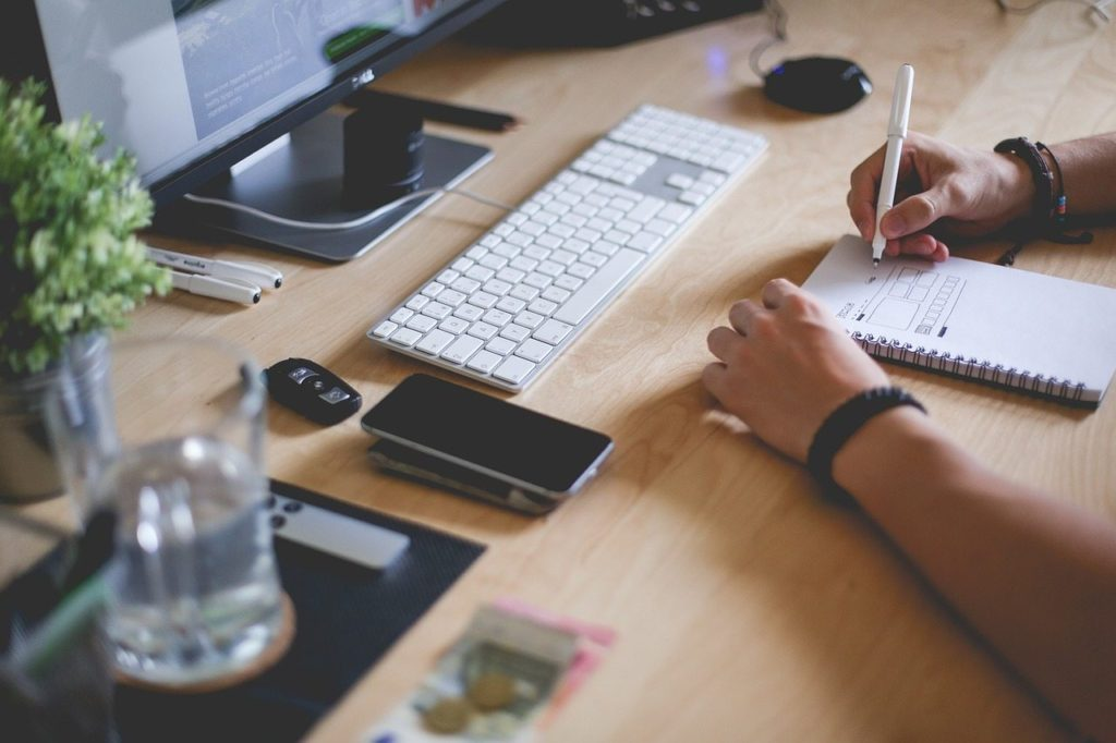 Escritorio con ordenador de sobremesa, móvil y alguien que toma notas en una libreta