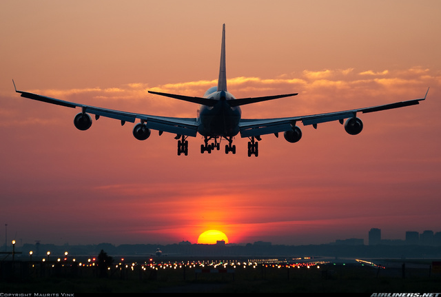 Un avión aterrizando al atardecer