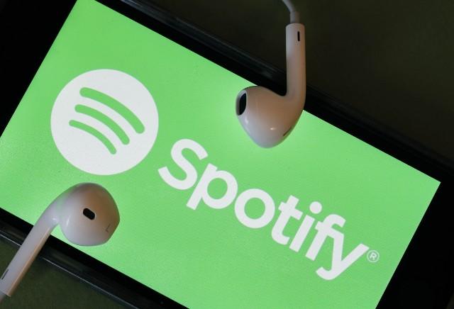 Un móvil con el logo de Spotify ocupando toda la pantalla y dos auriculares encima