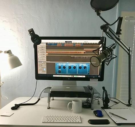 Una mesa de trabajo con un ordenador, micrófono de condensador, auriculares y libreta y boli