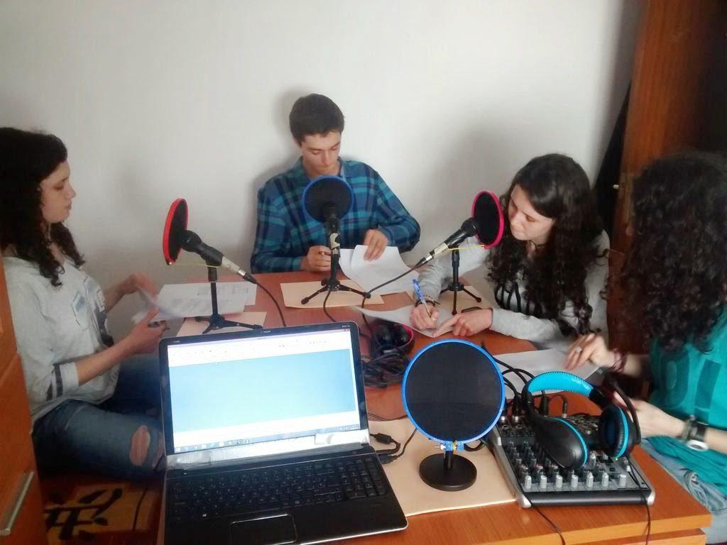 Cuatro chicos en una mesa con equipo para grabar podcasts