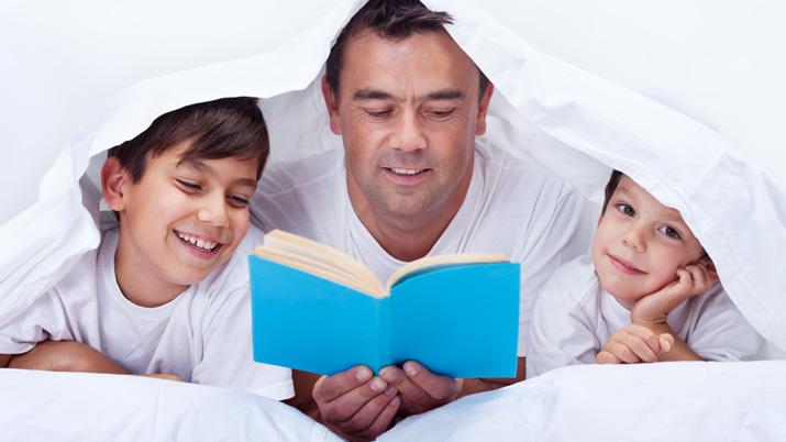 Un padre leyendo un cuento a sus dos hijos bajo una sábana