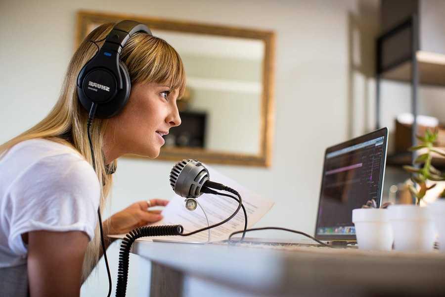 Una chica ante un micro grabando un podcast