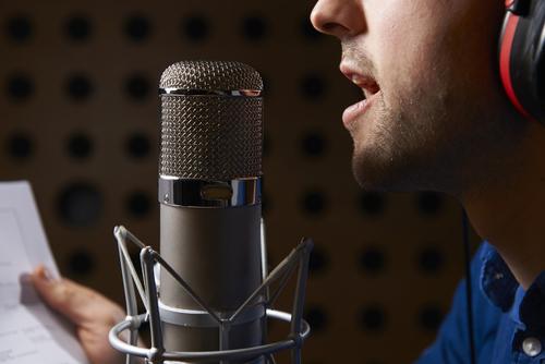 Un hombre leyendo un texto ante un micrófono de condensador