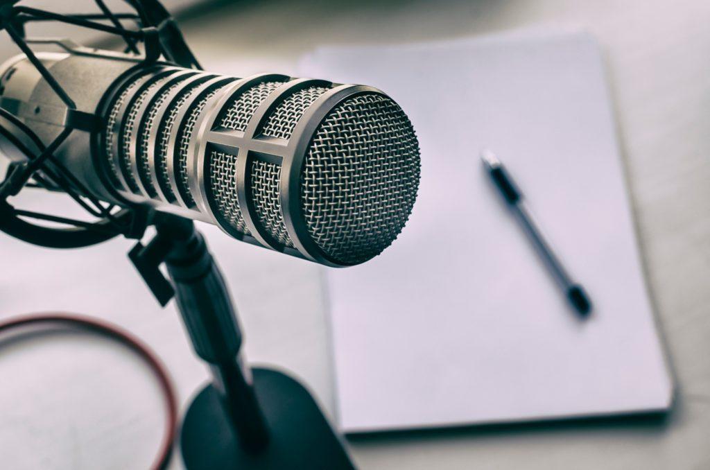 Un micrófono y al fondo una libreta con un boli
